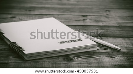 Black and White  pen on the closed notebook lying on a wooden table