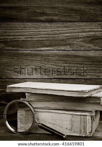 black and white photo. a pile of old books and magnifier on wooden background. the concept of the research, the study. with space for text - stock photo