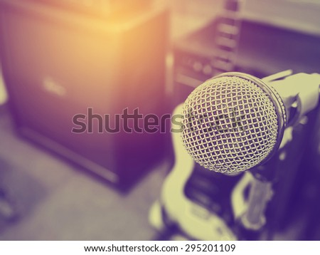 Black and white photo and lighting of The microphone in a recording studio or concert hall with amplifier in out of focus background. : Vintage style and filtered process. - stock photo