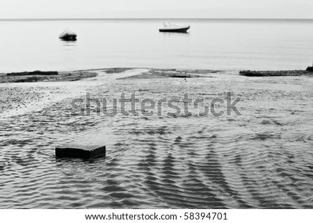 Black and white photo. Current water and stone in the foreground. Boats on the back. - stock photo