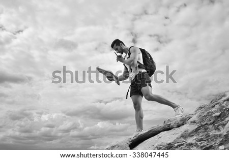 Black and white photo. Explorer talking via radio station. Young man tourist with a backpack standing on top of a mountain and holding map