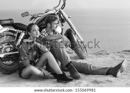 Black and white photo. Happy young love couple on scooter enjoying themselves on trip  - stock photo