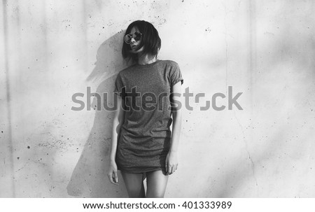 black-and-white photo of a attractive young girl dressed in a gray blank t-shirt posing against a background of a concrete wall in the rays of the setting sun