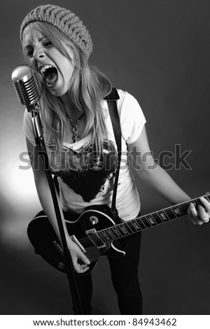 Black and white photo of a blond female screaming into an old microphone and playing electric guitar.  High contrast with film grain added.