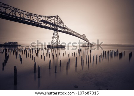 Black and White photo of a bridge in the fog - stock photo