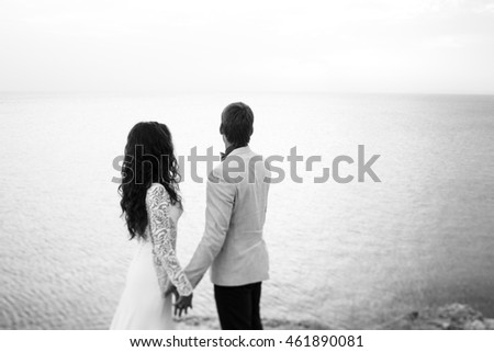 Black and white photo of a couple admiring the sea