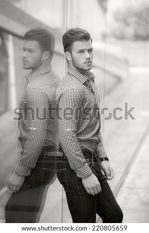 Black and white photo of a handsome young man wearing a shirt and jeans. Street shooting in Timisoara, Romania  - stock photo