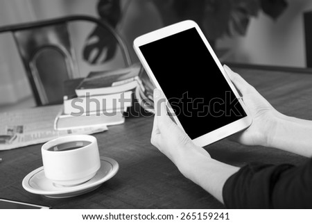 Black and white photo of a woman holding a tablet with no name coffee cup and a stack of books in background on a wood table with shallow depth of field - stock photo