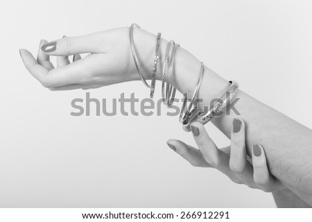 Black and white photo of a woman with nice nails showing jewel on her arm with her hands on a light gray background
