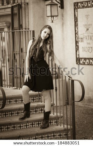 Black and white photo of a young women in black dress - stock photo