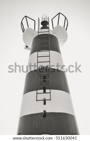 Black and white photo of amazing lighthouse on blue sky background with brightly shining sun