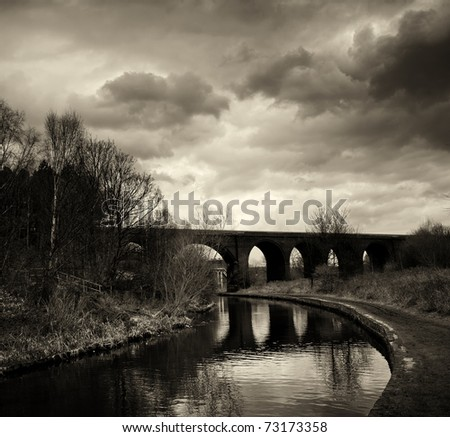 Black and white photo of an arc bridge with dramatic sky in Huddersfield. - stock photo