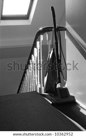 Black and White photo of an old-fashioned vacuum cleaner at the top of a staircase with wooden banister lit from behind by a skylight window - stock photo