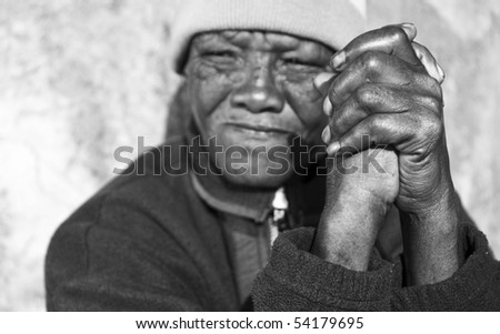 Black and white photo of an senior african woman with folded hands - focus on the weathered hands - stock photo