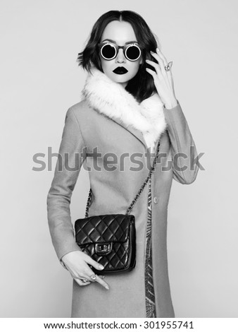 Black and white photo of beautiful brunette model in fashion clothes posing in studio. Wearing coat, handbag, sunglasses - stock photo