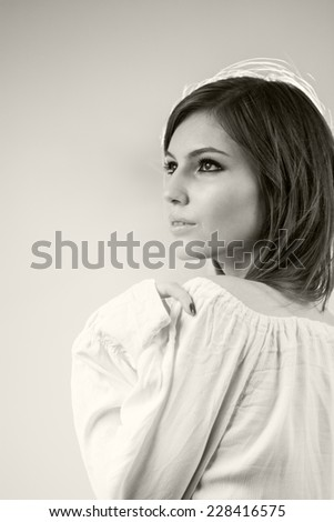 Black and white photo of beautiful caucasian girl wearing a white blouse with light grey background