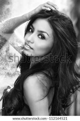 Black and white photo of beautiful elegant model with gorgeous long dark hair - stock photo