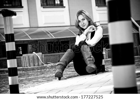 Black and white photo of beautiful woman sitting on pavement