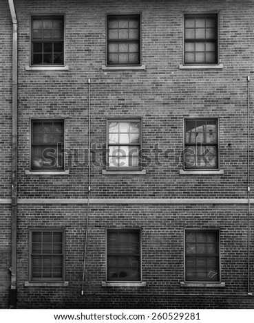 Black and white photo of brick facade with windows - stock photo