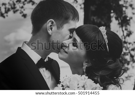 black and white photo of bride and groom kissing on the background of trees.