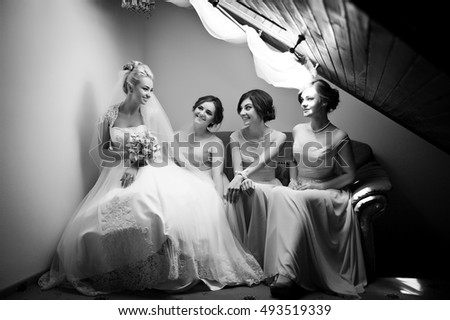 Black and white photo of charming bride and her pretty bridesmaids sitting on the couch