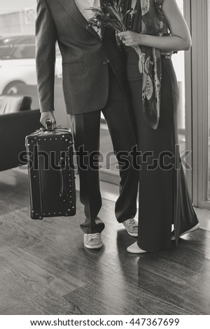 Black and white photo of couple at the reception desk holding leather vintage style suitcase trunk, interior background - stock photo