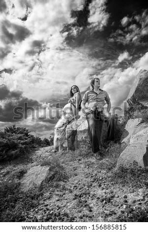 Black and white photo of couple sitting on rock - stock photo