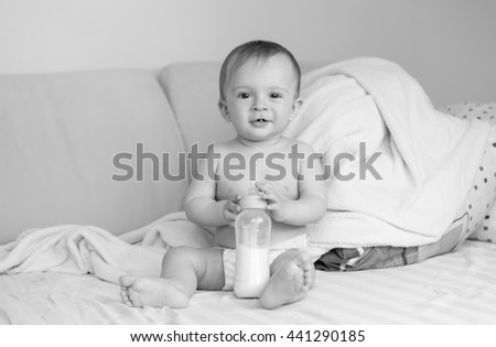 Black and white photo of cute baby boy sitting on bed with milk bottle - stock photo