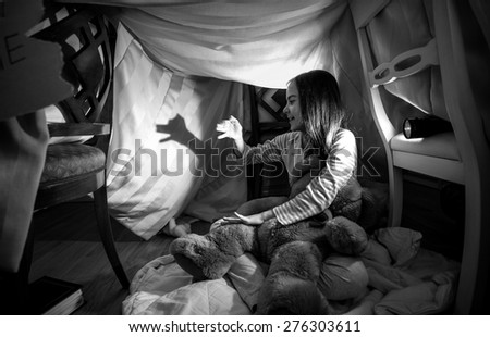 Black and white photo of cute girl making shadow of dog with hands and flashlight - stock photo
