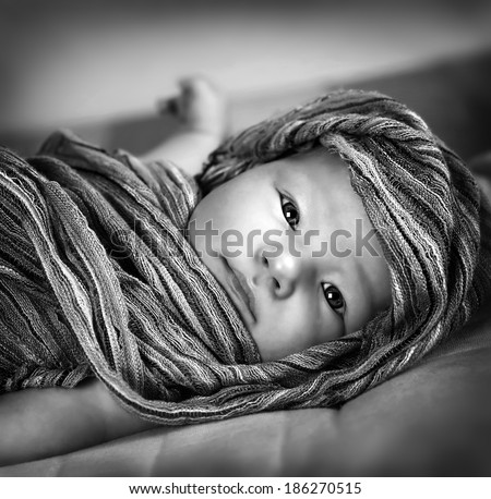 Black and white photo of cute little baby girl wrapped in scarf, lying down on the bed, kids fashion concept  - stock photo