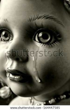 Black and white photo of,doll with tears.