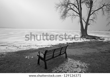 Black and White photo of empty bench overlooking frozen lake - stock photo