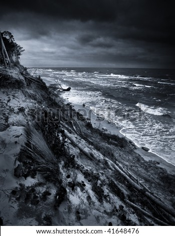 Black and white photo of eroded coast at baltic sea due climate change - stock photo