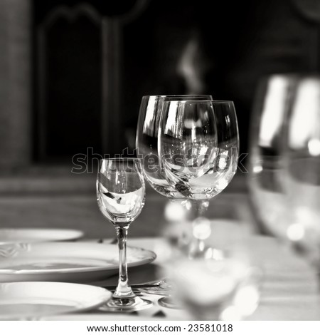black and white photo of glass goblets on the table - stock photo