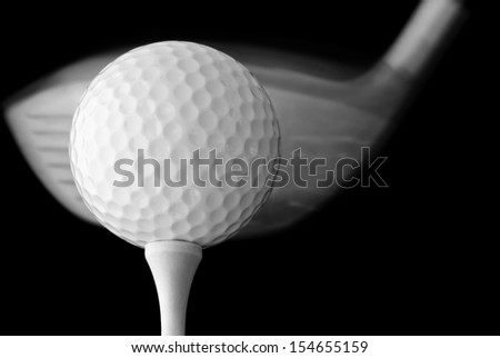 Black and white photo of golf ball on tee with driver in motion - about to make contact. Macro with extremely shallow dof on black background.  - stock photo