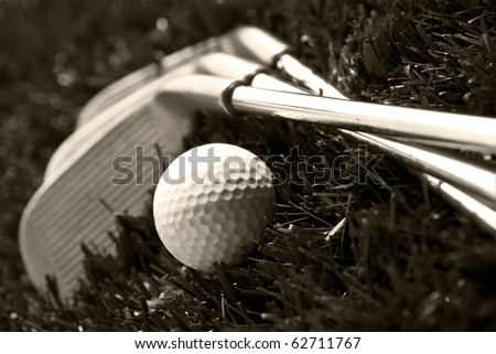 Black and white photo of golf clubs and a golf ball in low light for contrast - stock photo