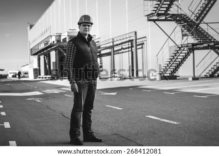 Black and white photo of handsome engineer standing on building site - stock photo