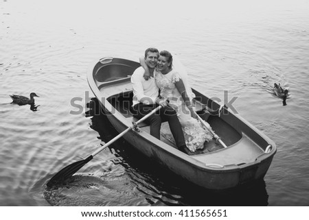 Black and white photo of happy bride and groom posing on old rowing boat - stock photo