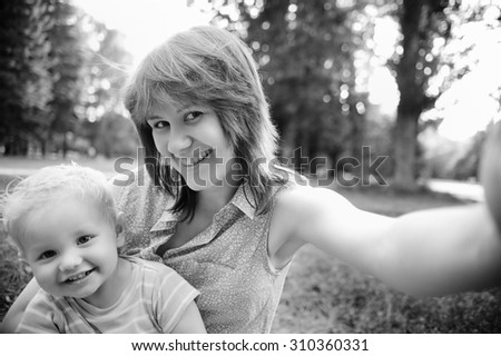 Black and white photo of happy family mother and her adorable toddler son at park making selfie - stock photo