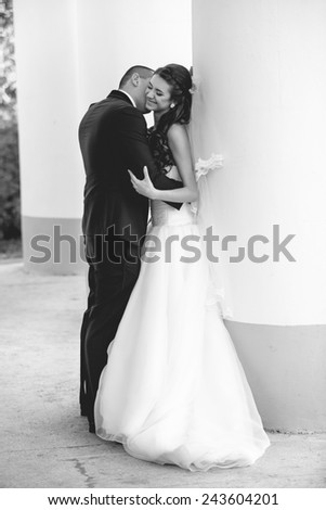 Black and white photo of happy just married couple kissing against row of big columns - stock photo