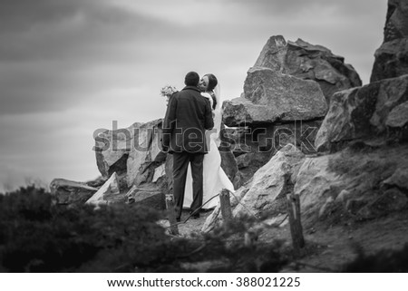 Black and white photo of kissing bride and groom on top of high mountain - stock photo