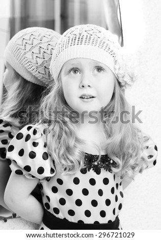Black and white photo of little girl in dress at mirror - stock photo