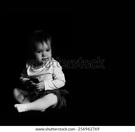black and white photo of little girl with phone