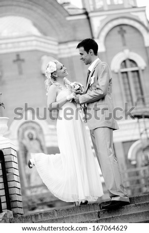 Black and white photo of married couple holding hands and looking at each other on street - stock photo