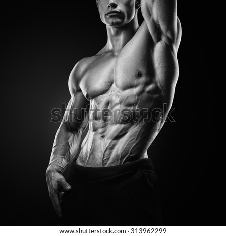 Black and white photo of Muscular and fit young fitness model posing over black background. Strong bodybuilder with six pack, perfect abs, shoulders, biceps, triceps and chest. - stock photo