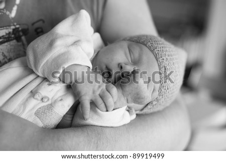 black and white  photo of newborn sleeping in his father hands - stock photo