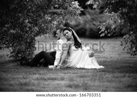 Black and white photo of newly married couple sitting back to back on grass at park - stock photo