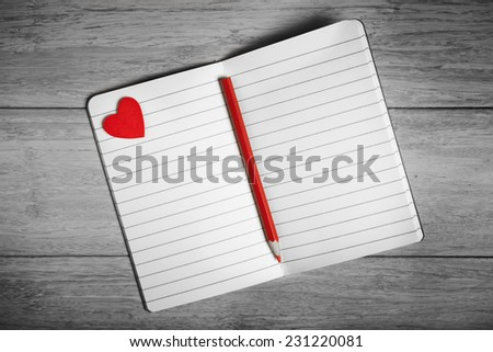 Black and white photo of open notebook with red heart and pencil - stock photo