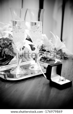 Black and white photo of opened box with wedding rings against two glasses of champagne