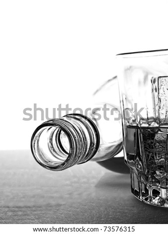 Black and white photo of overturned whiskey bottle and glass in front of white background. - stock photo